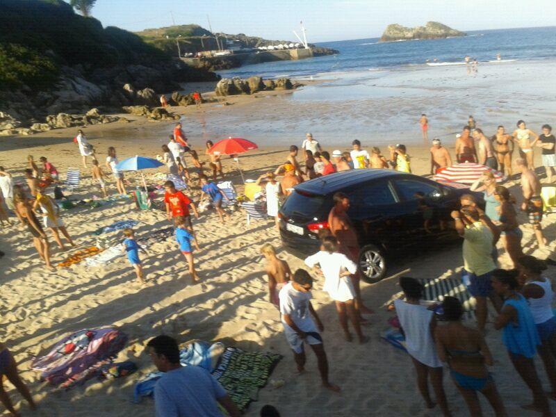 El momento en el que el coche invade la arena ante el asombro de los bañistas presentes - Celoriu.com