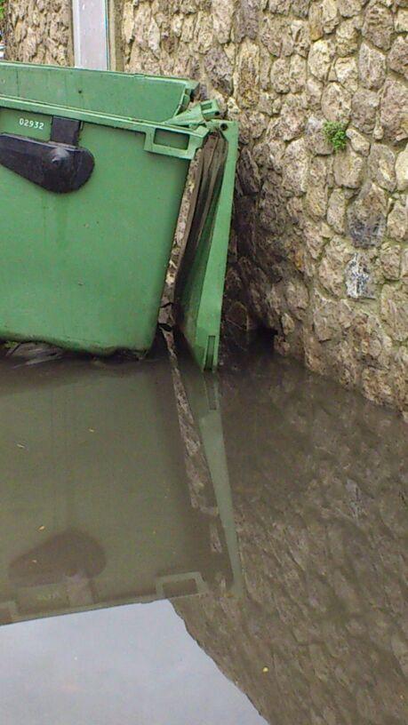 Detrás del contenedor, una de las tragaderas posiblemente taponadas que podrían ser causa de las inundaciones - Celoriu.com